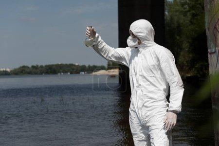 Photo pour Inspecteur de l'eau dans le fiole protecteur de fixation de costume avec l'échantillon d'eau à la rivière - image libre de droit