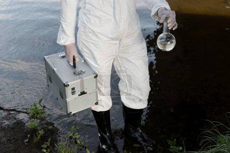 Photo pour Vue partielle de l'inspecteur d'eau dans le kit protecteur de fixation de costume et le flacon à la rivière - image libre de droit