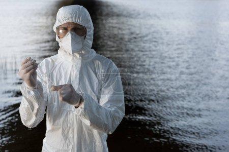 Photo pour Inspecteur de l'eau en costume de protection, lunettes et respirateur prélevant un échantillon d'eau à la rivière - image libre de droit