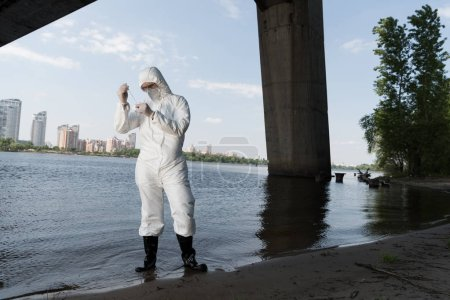 Photo for Full length view of water inspector in protective costume and respirator taking water sample at river - Royalty Free Image