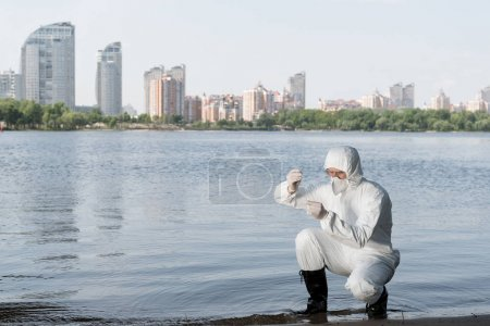 Photo for Water inspector in protective costume and respirator taking water sample at river - Royalty Free Image