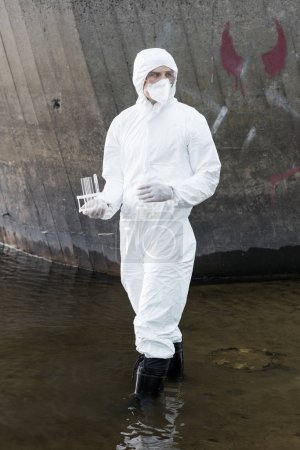 Foto de Full length view of water inspector in protective costume and respirator holding test tubes and flask at river - Imagen libre de derechos