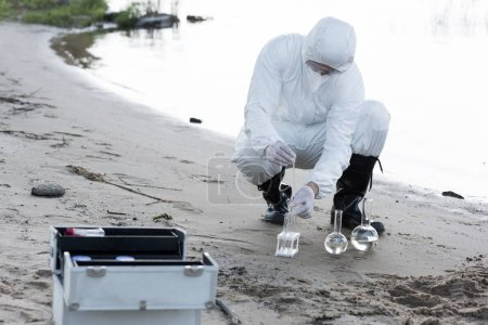 Photo for Water inspector in protective costume and respirator taking water samples at river - Royalty Free Image