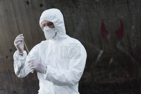 Photo pour Inspecteur de l'eau en costume de protection et respirateur prélevant l'échantillon d'eau - image libre de droit