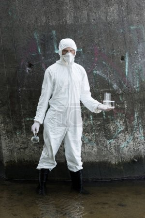 Photo for Full length view of water inspector in protective costume and respirator holding test tubes and flask with water samples at river - Royalty Free Image