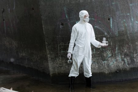 full length view of water inspector in protective costume and respirator holding test tubes and flask with water samples at river
