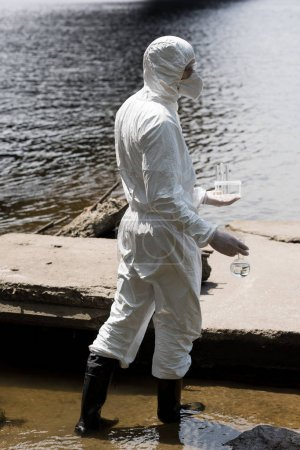 Photo for Side view of water inspector in protective costume and respirator holding test tubes and flask with water samples at river - Royalty Free Image
