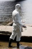 """Постер, картина, фотообои """"вид воды инспектора в защитном костюме и респираторе, держащем пробирки и колбу с пробами воды у реки"""""""