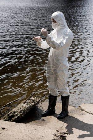 Photo pour Vue pleine longueur de l'inspecteur d'eau dans le costume protecteur, les gants de latex et le respirateur prenant l'échantillon d'eau à la rivière - image libre de droit