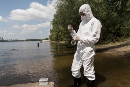 Photo pour Water inspector in protective costume, latex gloves and respirator taking water sample at river - image libre de droit