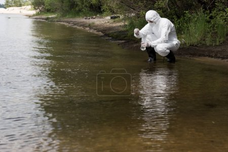 Photo for Water inspector in protective costume, latex gloves and respirator taking water sample at river - Royalty Free Image