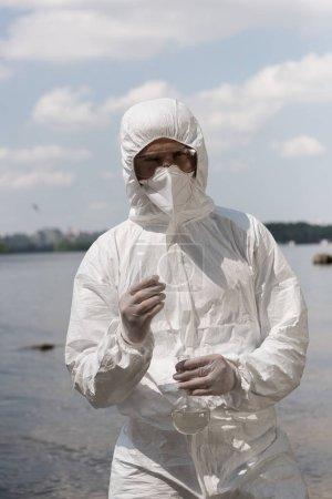 Foto de Vista frontal del inspector de agua en traje protector, guantes de látex y frasco de sujeción matraz con muestra de agua en el río - Imagen libre de derechos