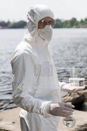 Photo pour Inspecteur de l'eau en costume de protection, gants en latex et respirateur tenant flacon et tubes à essai avec des échantillons d'eau à la rivière - image libre de droit