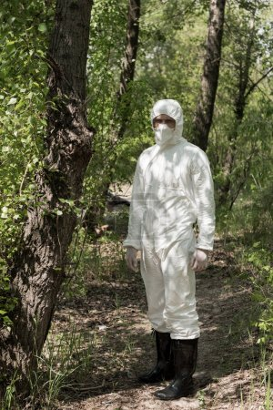 Photo for Full length view of ecologist in protective costume and respirator in forest - Royalty Free Image
