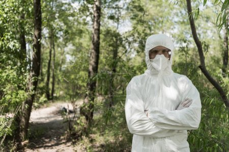 Foto de Front view of ecologist in protective costume and respirator with crossed arms in forest - Imagen libre de derechos