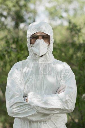 Photo pour Vue avant de l'écologiste dans le costume protecteur et le respirateur avec les bras croisés dans la forêt - image libre de droit