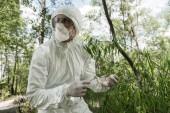 """Постер, картина, фотообои """"эколог в защитном костюме и респиратор трогательные листья деревьев в лесу"""""""