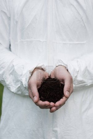 Photo for Partial view of ecologist in protective costume holding handful of soil - Royalty Free Image