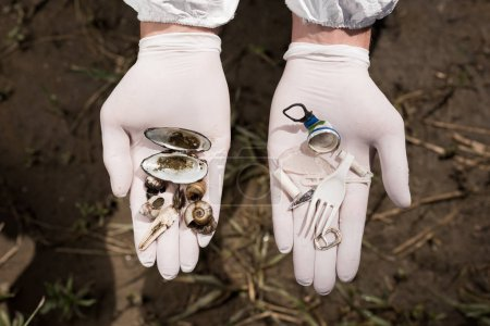 Photo for Cropped view of ecologist in latex gloves holding plastic garbage and - Royalty Free Image