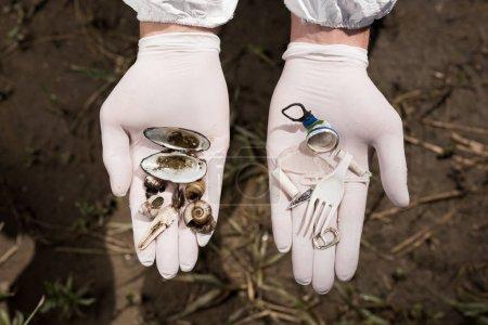 Photo pour Vue recadrée de l'écologiste dans des gants en latex tenant des ordures en plastique et - image libre de droit