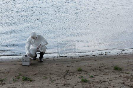 Photo pour Inspecteur de l'eau en costume de protection et respirateur avec trousse d'inspection assis à la côte de la rivière - image libre de droit