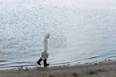 Photo for Full length view of water inspector in protective costume and respirator holding inspection kit while walking on river coast - Royalty Free Image