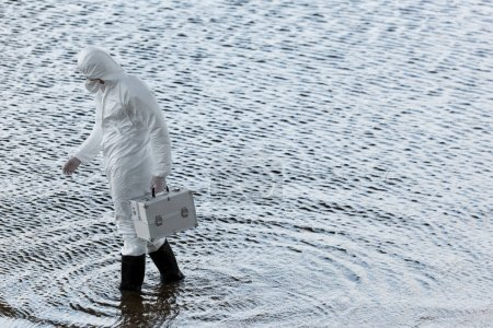 full length view of water inspector in protective costume holding inspection kit at river