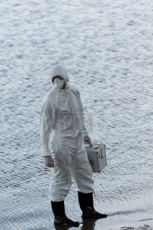 Foto de Full length view of water inspector in protective costume holding inspection kit at river - Imagen libre de derechos