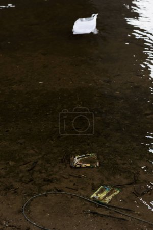Photo for Plastic garbage on textured sandy bottom in river - Royalty Free Image