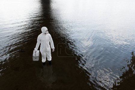 Foto de Overhead view of water inspector in protective costume holding inspection kit at river - Imagen libre de derechos