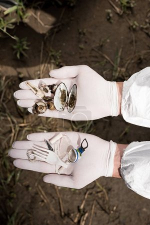 Photo for Cropped view of ecologist in latex gloves holding seashells and plastic garbage - Royalty Free Image