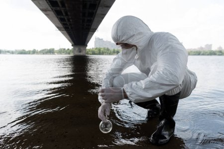 Photo for Water inspector in protective costume holding flask and taking water sample from river - Royalty Free Image