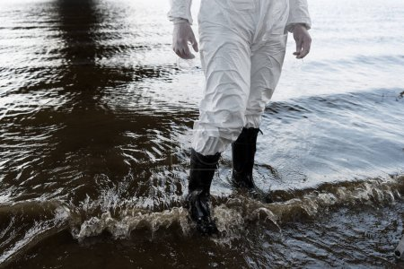 Photo for Partial view of water inspector in protective costume and boots standing in river - Royalty Free Image
