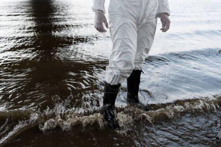 Foto de Vista parcial del inspector de agua en traje protector y botas de pie en el río - Imagen libre de derechos