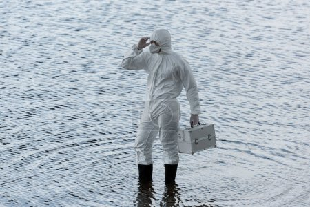 Photo for Water inspector in protective costume holding inspection kit in river - Royalty Free Image