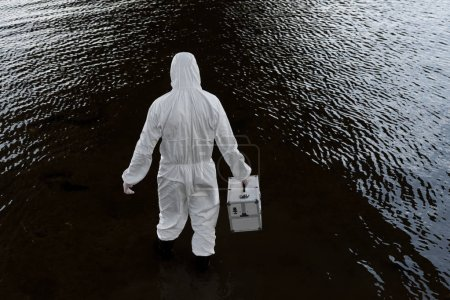 Photo for Back view of water inspector in protective costume holding inspection kit in river - Royalty Free Image