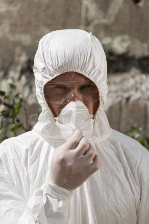 Photo for Front view of ecologist in protective costume and goggles taking off respirator - Royalty Free Image