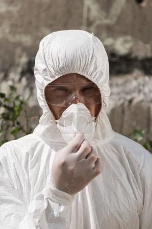 Photo pour Vue avant de l'écologiste dans le costume protecteur et les lunettes enlevant le respirateur - image libre de droit