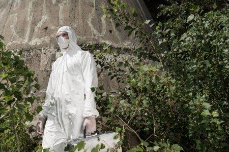 Photo pour Vue à faible angle de l'écologiste avec kit d'inspection debout près des plantes - image libre de droit