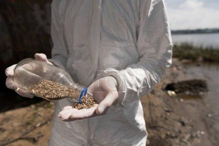 Foto de Vista recortada del ecologista en traje protector sosteniendo botella con guijarros - Imagen libre de derechos
