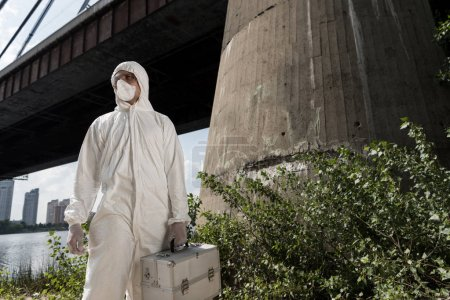 Foto de Ecologist in protective costume with inspection kit standing near bridge - Imagen libre de derechos