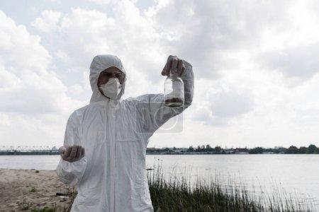 Foto de Ecologista en traje protector y botella de retención de respirador con muestra de suelo - Imagen libre de derechos