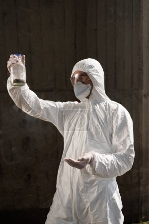 Photo for Ecologist in protective costume and respirator holding bottle with soil sample - Royalty Free Image