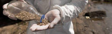 Photo pour Tir panoramique de l'écologiste dans des gants en latex tenant la bouteille avec des cailloux - image libre de droit