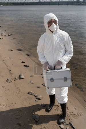 Foto de Full length view of water inspector in protective costume, respirator and goggles holding inspection kit on river coast - Imagen libre de derechos