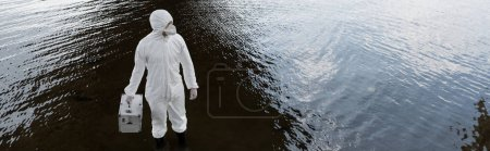 Photo for Panoramic shot of water inspector in protective costume and respirator holding inspection kit at river - Royalty Free Image