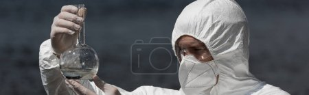 Photo for Panoramic shot of water inspector in respirator and goggles holding flask with water sample - Royalty Free Image