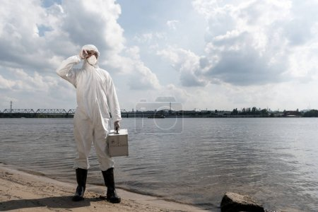 Foto de Full length view of water inspector in protective costume holding inspection kit at river coast - Imagen libre de derechos