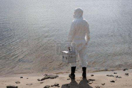 Photo pour Vue arrière de l'inspecteur d'eau dans le kit protecteur d'inspection de fixation de costume à la côte de fleuve - image libre de droit