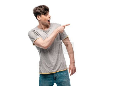 Photo for Surprised young man pointing with finger and looking away isolated on white - Royalty Free Image
